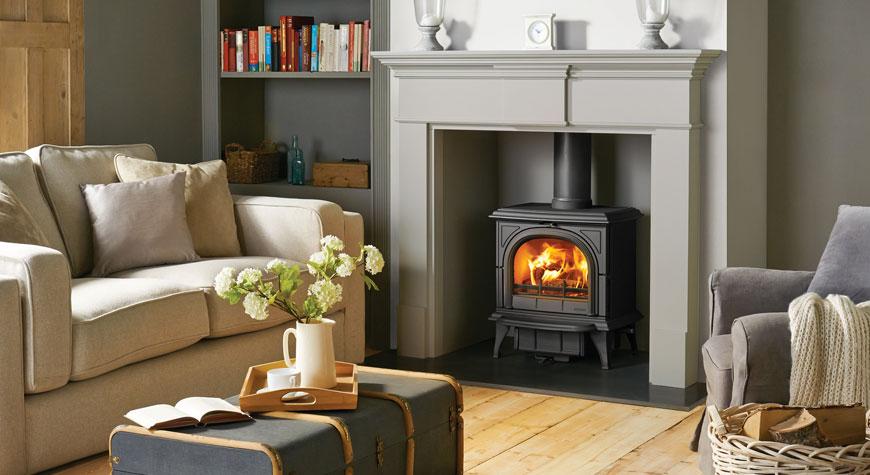 Le poêle à bois Huntingdon 30 de Stovax en noir mat avec porte claire et chambranle Pembroke en gris