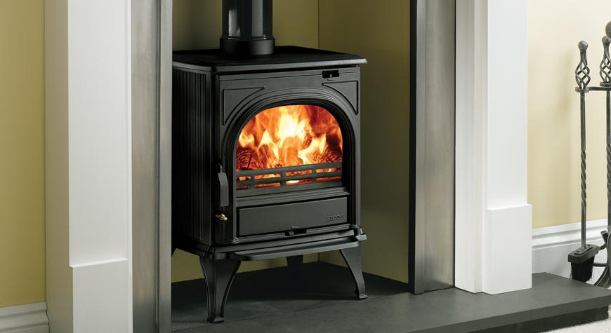 Le poêle à bois Huntingdon 25 de Stovax en noir mat avec porte claire et brûlant des bûches.