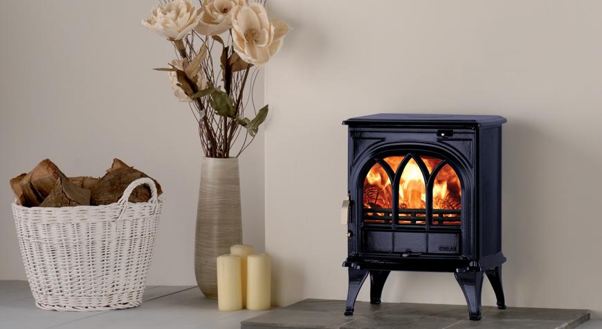 Le poêle à bois Huntingdon 25 de Stovax en bleu nuit émaillé avec porte gothique et brûlant des bûches.