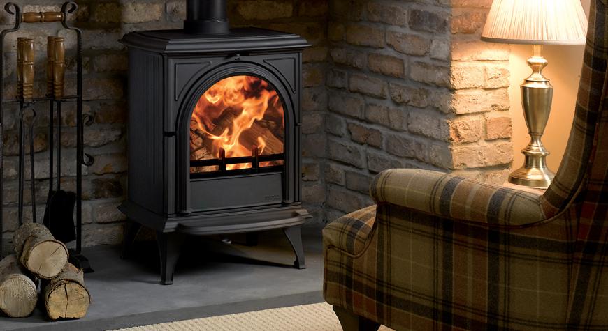 Le poêle à bois Huntingdon 28 de Stovax en noir mat avec porte claire et brûlant des bûches.