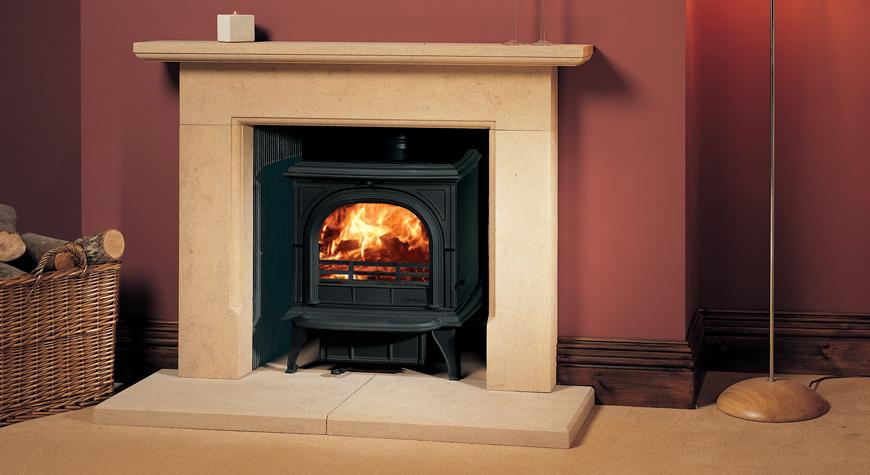 Le poêle à bois Huntingdon 30 de Stovax en noir mat avec porte claire et brûlant des bûches.