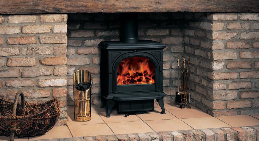 Le poêle à bois Huntingdon 30 de Stovax en noir mat avec porte claire et brûlant des combustibles sans fumée.