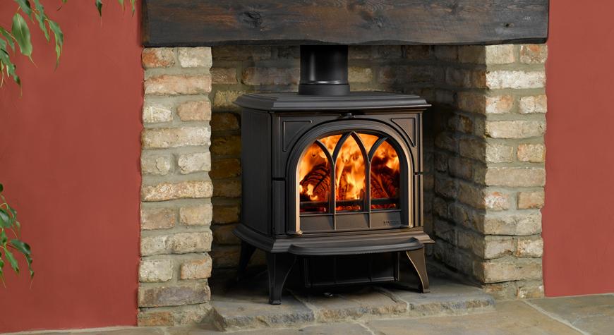 Le poêle à bois Huntigndon 30 de Stovax en noir mat avec porte gothique et brûlant des bûches.