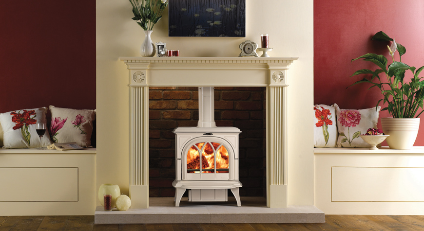 Le poêle à bois Huntingdon 30 de Stovax en ivoire émaillé avec porte gothique et brûlant des bûches.
