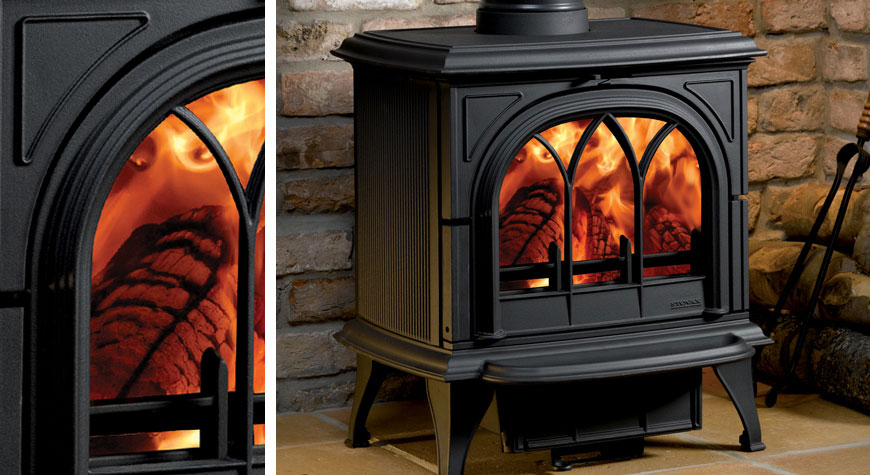 Le poêle à bois Huntingdon 30 de Stovax en noir mat avec porte gothique et brûlant des bûches.