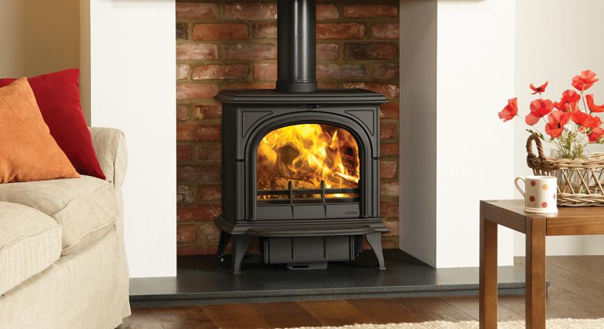 Le poêle à bois Huntingdon 40 de Stovax en noir mat avec porte claire et brûlant des bûches.