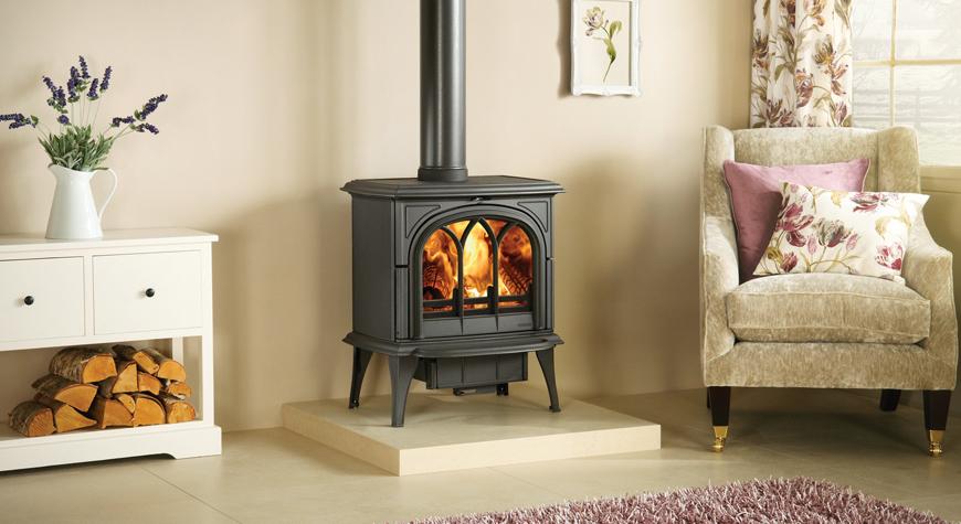 Le poêle à bois Huntingdon 40 de Stovax en noir mat avec porte gothique et brûlant des bûches.