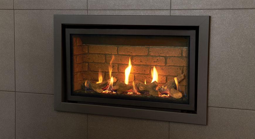 L'insert à gaz Studio 1 Slimline Profil finition Anthracite, lit de combustibles effet bûches et revêtement de foyer effet briques.
