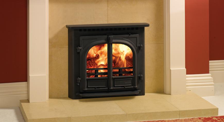 L'insert Stockton 8 de Stovax avec dessus plat en noir mat et brûlant des bûches.  Également en photo : Le chambranle de cheminée Pembroke de Stovax.